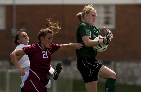 Junior goalkeeper Libby Stout rises above freshman defender Katrina Ott and Minnesota defender Kylie Kallman to gain control of the ball during the second half of their game at the WKU Soccer Field on Sunday afternoon. The Toppers lost 2-1.