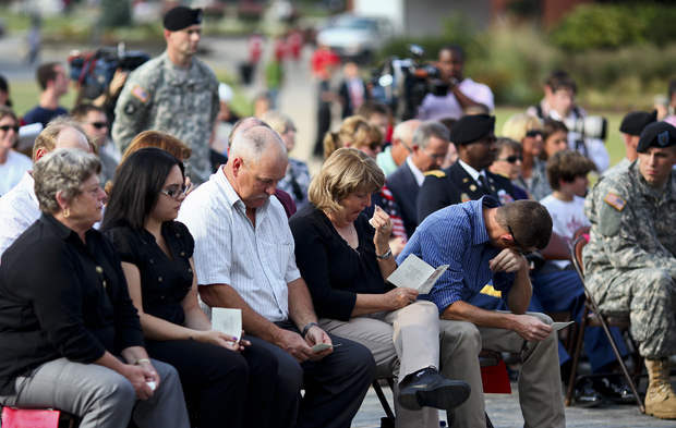 (From right) Brother Nathan Yates, mother Cathy Yates, and father David Yates mourn during a memorial service for 1st Lt. Eric D. Yates at the foot of the Guthrie Bell Tower on the South Lawn of Western Kentucky University on Thursday. A 2008 graduate of Western, 1st Lt. Yates was killed in battle in the Kandahar Province of Afghanistan after being hit by an improvised explosive device while on foot patrol with the 101st Airborne Division. LUKE SHARRETT/HERALD