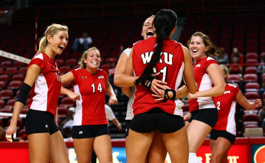The Lady Toppers rally around senior Emily Teegarden on Friday. WKU split two matches, losing to Virginia Tech in five sets before knocking off then-undefeated Missouri in four.