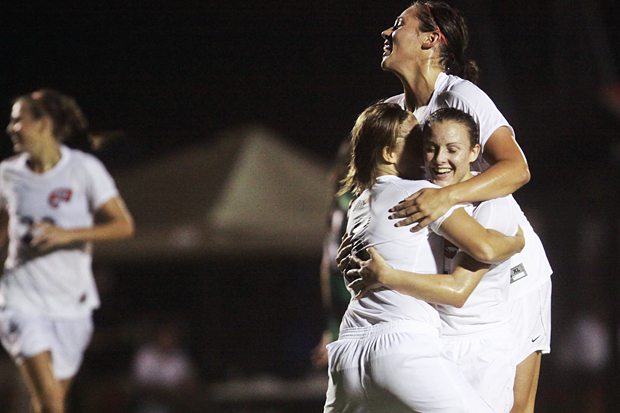 Mallory Outerbridge, left, and Sydney Sisler, top, hug Christen Sims after Sims netted the go-ahead goal against North Texas. The Lady Toppers won by a 1-0 score.