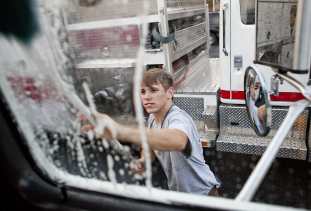 """Alex Solomito, a freshman from Memphis, Tenn., washes the fire trucks at Barren River Volunteer Fire Department Station 2 on Monday.  Solomito joined the fire department about four weeks ago after a friend and fellow student suggested he join. """"You get to help people,"""