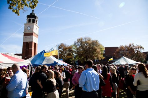 A crowd of tailgaters gathers on South Lawn under the Guthrie Bell Tower before WKU