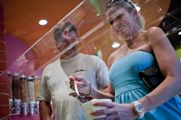 Chad Turner, left,  of Atlanta, Ga., and Joanna Futrell, of Bowling Green, top their frozen yogurt with toppings at Stakz. Stakz is a new frozen yogurt store on Scottsville Road, which offers 12 varieties of yogurt and over 50 toppings. LANCE BOOTH/HERALD