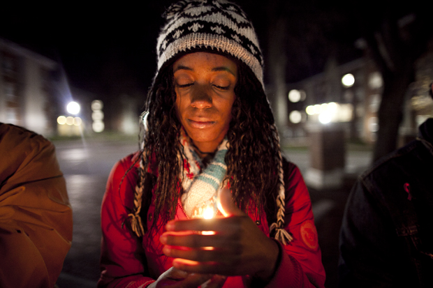 """Jasmine Bowie, a senior from Mannheim, Germany, protected her flame from the wind as she stood outside in the 35-degree weather during the candlelight vigil for HIV/AIDS awareness at Centennial Mall. The event organizer, Chad Beswick, invited attendees to speak about their experiences with HIV/AIDS. He said that he was excited to see that the amount of people who attended the vigil had tripled since last year and said, """"We need to realize this every day, not just once a year."""""""