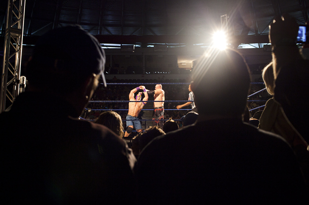 """World Wrestling Entertainment wrestler Kane tries to pull off a lucha libre mask worn by John """"Juan"""" Cena during a WWE match at Diddle Arena. The non-televised event is a break from bigger shows. Fans can get a more intimate experience with superstars such as The Miz, The Undertaker, Triple H and more."""
