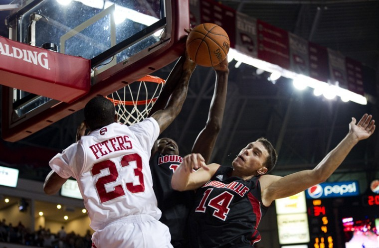 Freshman guard Brandon Peters unsuccessfully goes up for a basket against Louisville's Kyle Kuric and Gorgui Dieng in WKU's 114-82 loss to the Cardinals.