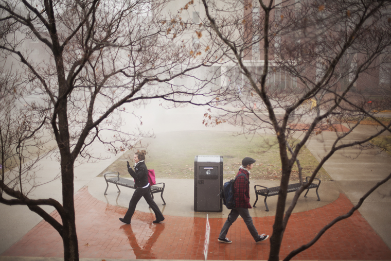 """Students walk past a solar compactor in the snow between classes outside of Downing University Center and Minton Hall on Monday afternoon. WKU is continuing a """"go green"""" initiative this semester."""