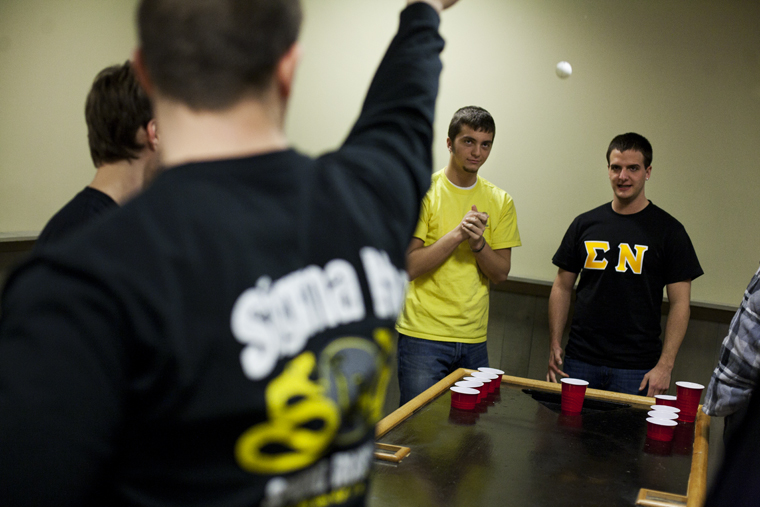 Bowling Green freshman Dylan Sherman, right, and Evansville senior Adam Merrick, second from right, watch the opposing Sigma Nu players shoot during a game of water pong in the new Sigma Nu house during Rush this week.