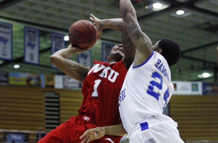 MTSU freshman Kerry Hammonds attempts to block WKU senior Sergio Kerusch during the Toppers' game at MTSU on Saturday. The Toppers lost 57-39, assuring them of a third-place finish in the Sun Belt East.