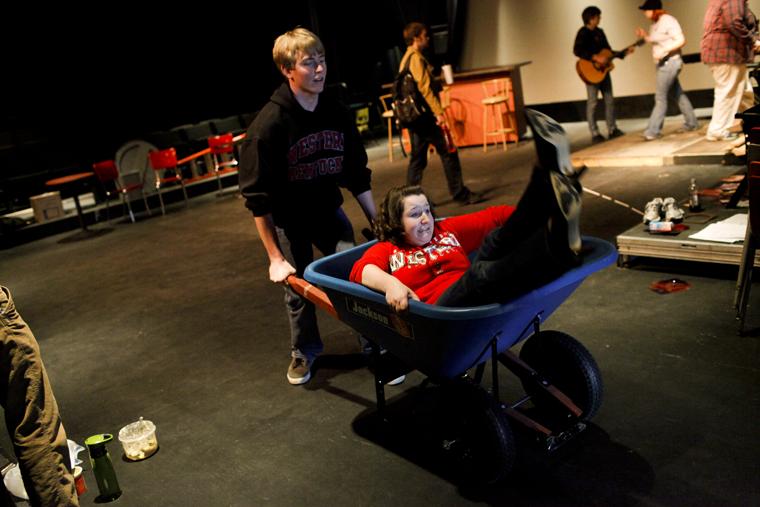 Florence freshman Nic Baynum pushes Louisville freshman J. Morgan Shaffo in a wheelbarrow while practicing the song