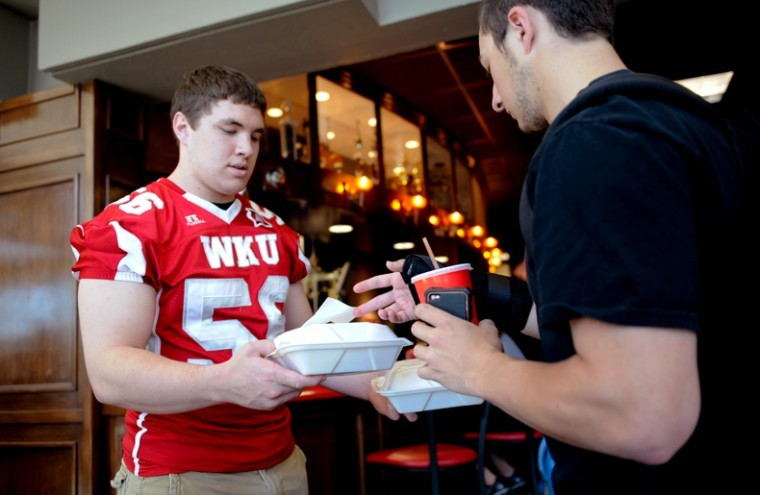 Freshman+linebacker+Matt+Smith+delivers+food+in+Red+Zone+Thursday+afternoon.+Smith%2C+a+Bowling+Green+resident%2C+said+he+and+other+WKU+football+players+were+helping++to+get+to+know+the+students%2C+and+so+the+students+can+get+to+know+us.