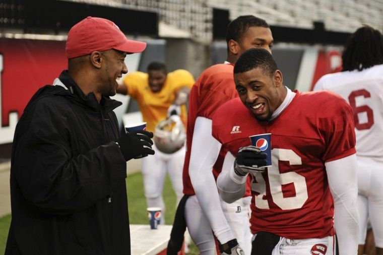 Head Coach Willie Taggart laughs with junior defensive back Kareem Peterson during a water break at WKU's spring practice Friday afternoon at Houchens-Smith Stadium.