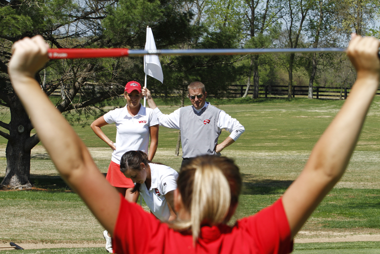 Sophomore Kelsey Burrell, senior JoAnna Smith, back left, and WKU head women's golf coach Ron Burchett, back right, watch as sophomore Kristen Wilkinson putts Wednesday at the Bowling Green Country Club during practice.