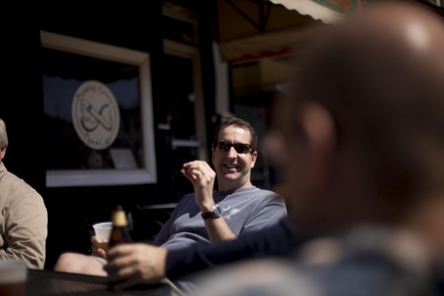 Bill Hall of Bowling Green talks with a group of men outside Bowling Green Pipe and Cigar on Saturday. Customers sat outside smoking cigars and drinking beer in the warm weather.