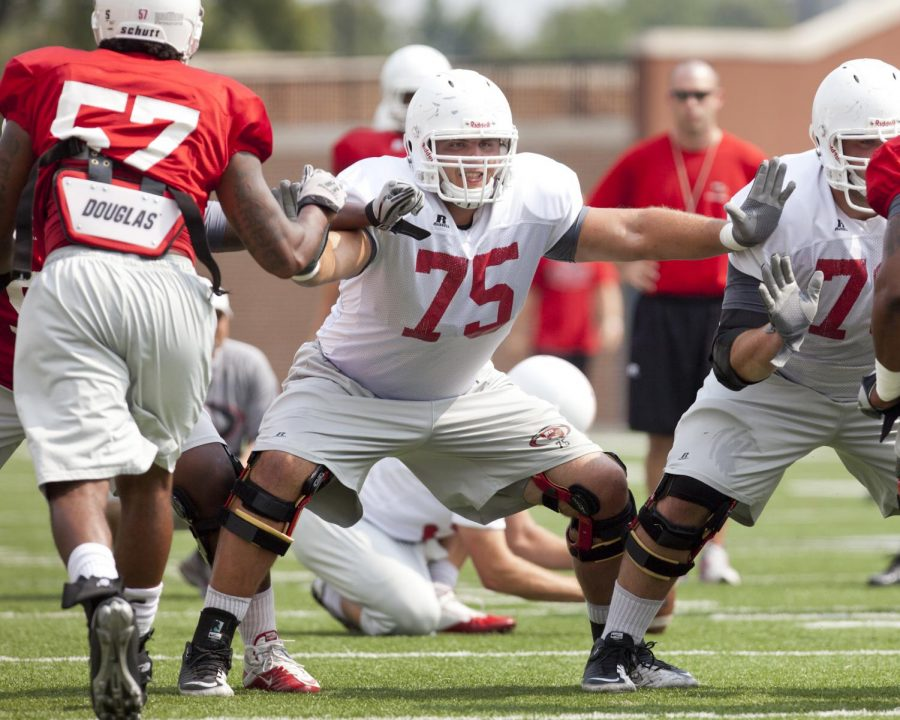 Offensive lineman Seth White (75) blocks during an extra point drill at practice at Smith Stadium on Aug. 25, 2011.