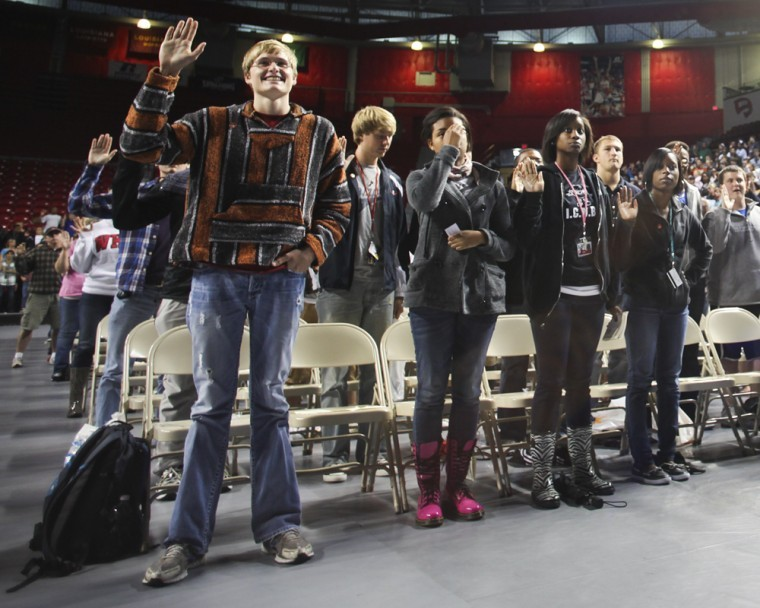 The class of 2015 raises their right hands while making an oath to President Gary Randsell to graduate on Tuesday during the Freshman Assembly in Diddle Arena.