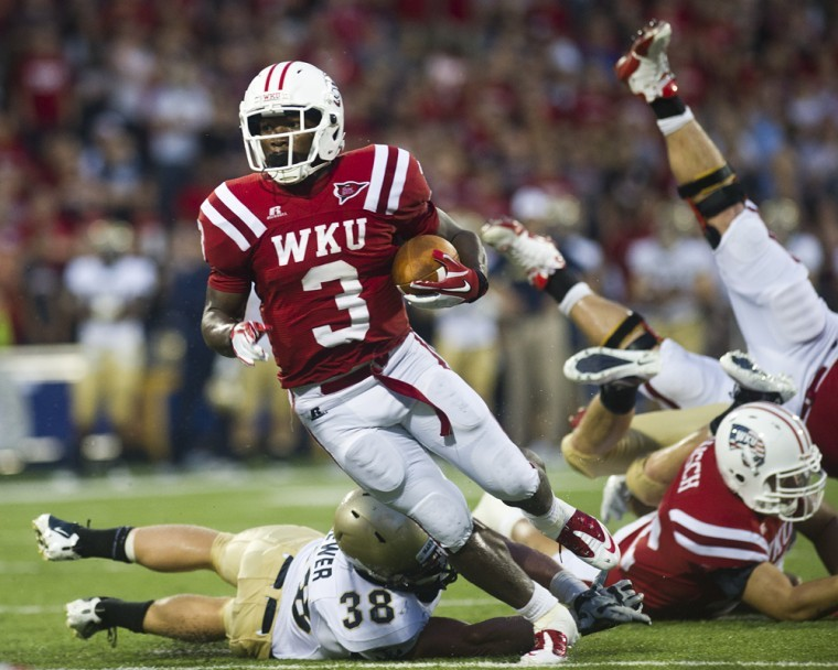 Bobby+Rainey+stays+just+out+of+the+grasp+of+a+Navy+defensive%0Alinebacker+during+a+13+yard+run+for+a+touchdown+in+the+second%0Aquarter+during+WKU%27s+40-14+lose+at+Smith+Stadium.%0A