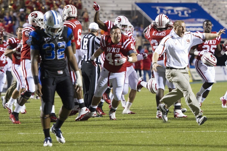 WKU players and coaches rush the field after beating MTSU in double overtime at Floyd Stadium on Oct. 6, 2011. WKU won the game 36-33.