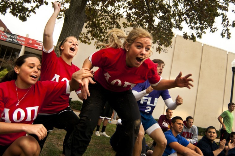 Hannah Blair (far left) of Owensboro and and Mary Clayton (middle) of Franklin cheer on fellow Alpha Omicron Pi sisters during the dizzy bat competition Tuesday on South Lawn. Alpha Omicron Pi placed second. The different competitions in the Greek Games were opportunities for sororities and fraternities to earn homecoming points.
