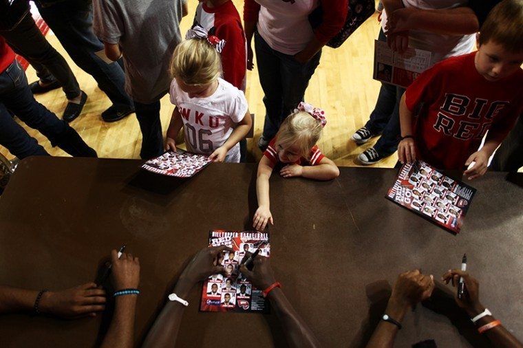 Kennedy Helm, 3, of Bowling Green waits in line for signatures from the men's basketball team during Hilltopper Hysteria on Friday night in Diddle Arena.