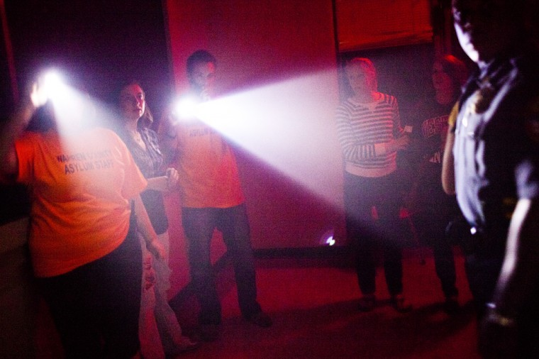 """People walk through the Warren County Asylum on Friday in Bowling Green. The """"Cancer Cops"""" Relay For Life team has organized the haunted house that will run during the weekends in October."""