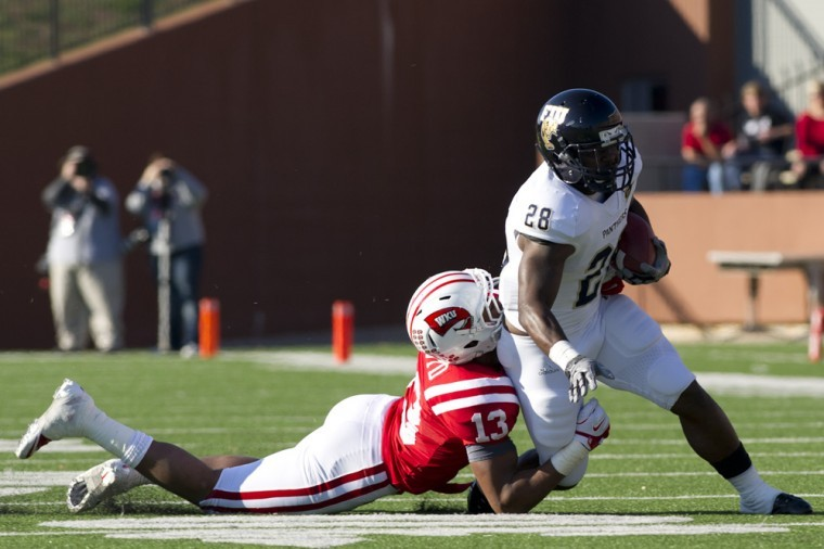 FIU+running+back+Darriet+Perry+is+taken+down+by+WKU%27s+sophomore%0Astrongside+linebacker+Xavius+Boyd+in+the+first+half.+WKU+beat+FIU%0A10-9.%0A