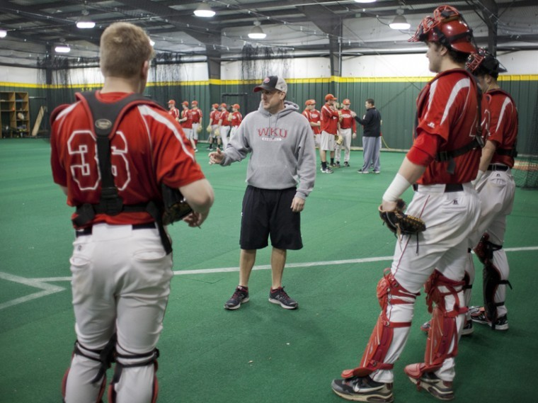 Assistant Coach Blake Allen talks to catchers during WKU's baseball team practice on Wednesday, January 25, inside the WKU baseball hitting facility.