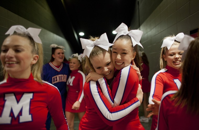 """Madison Central High School varsity cheerleader Lauren Abrams (left) celebrates with junior varsity cheerleader Emi Deck (right) after the varsity team completed their routine at the 2012 KAPOS State-At-Large Cheerleading Competition Saturday at Diddle. Madison Central won second place in the small varsity division of the competition. """"I think we did amazing. Couldn't do better,"""" Abrams said about her team's performance."""