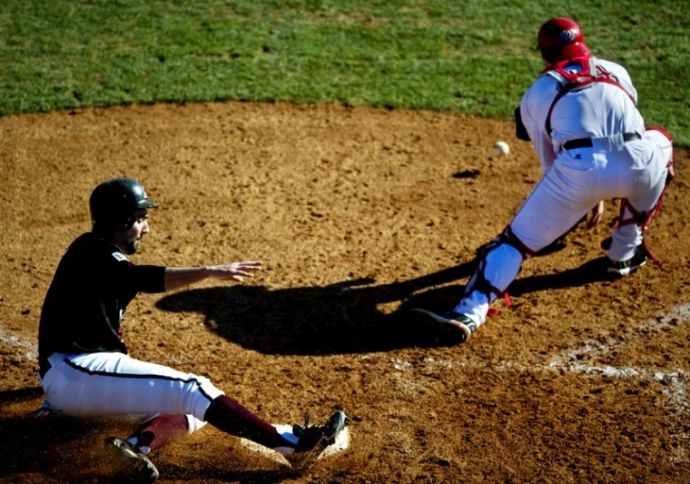 Southern Illinois first baseman Chris Serritella slides safely into home plate before WKU junior catcher Ryan Huck can field the throw from the outfield during the Toppers 8-3 loss on Sunday at Nick Denes Field.