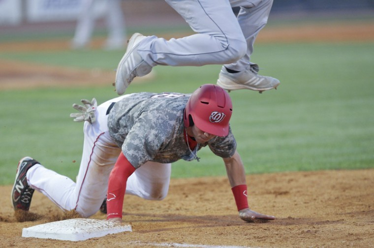 Junior+Steve+Hodgins+slides+back+to+first+under+a+leaping+FIU+first+baseman+at+Nick+Denes+Field+Friday+night.+WKU+lost+to+FIU+Friday+and+Saturday+before+winning+the+final+game+of+the+series.%0A