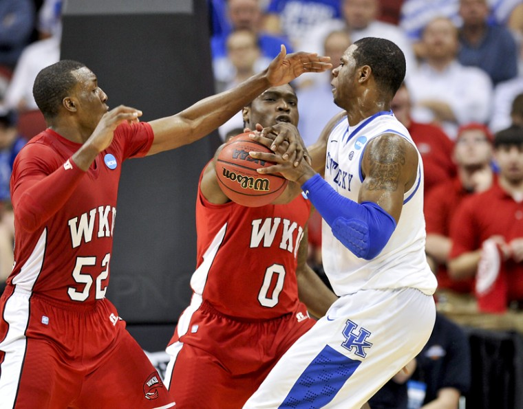 Freshman guard T.J. Price and sophomore forward Kene Anyigbo try to take the ball away from a UK player during the first round NCAA tournament game between WKU and UK at the YUM! Center in Louisville Thursday night. UK led WKU 45-26 at halftime.