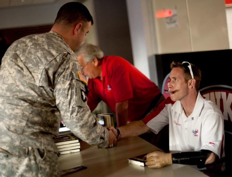 Tyler Rice, left, a WKU alumnus and captain in the National Guard, shakes hands with Bryan Anderson after Andersons keynote address in the Downing University Center Auditorium on Tuesday evening. Anderson lost both his legs and his left hand when he was hit by an IED during his second tour of duty in Iraq and has since lived his life to the fullest.