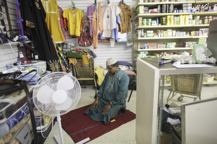 Ali Miah, who has owned and operated the International Supermarket on Broadway Avenue for the past six years, takes a break between customers to pray in a corner of his store.