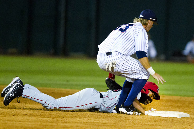 Outfielder, David Simmons, lies on the ground after sliding into second base and being tagged by outfielder, Mark Nelson, from Florida Atlantic University.The Hilltoppers lost 4-3 to FAU.