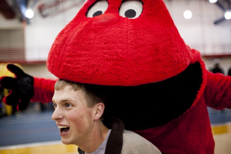 During the celebration for Big Red's birthday party at Preston Center, La Grange freshman Matthew Lawson has his picture taken with Big Red, who pretends to bite his head.