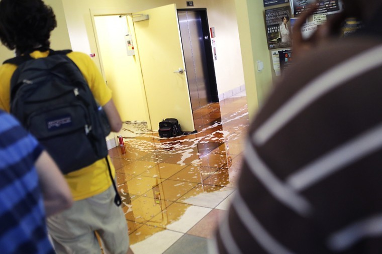 Hydraulic+fluid+from+an+elevator+spills+out+from+a+supply+closet+into+the+main+lobby+as+students+evacuate+Mass+Media+and+Technology+Hall%2C+Aug.+27%2C+2012.%0A