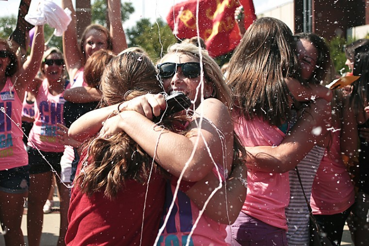 Chi Omega sisters, new and old, hug and cheer as they reunite during sorority recruitment bid day Sunday afternoon.