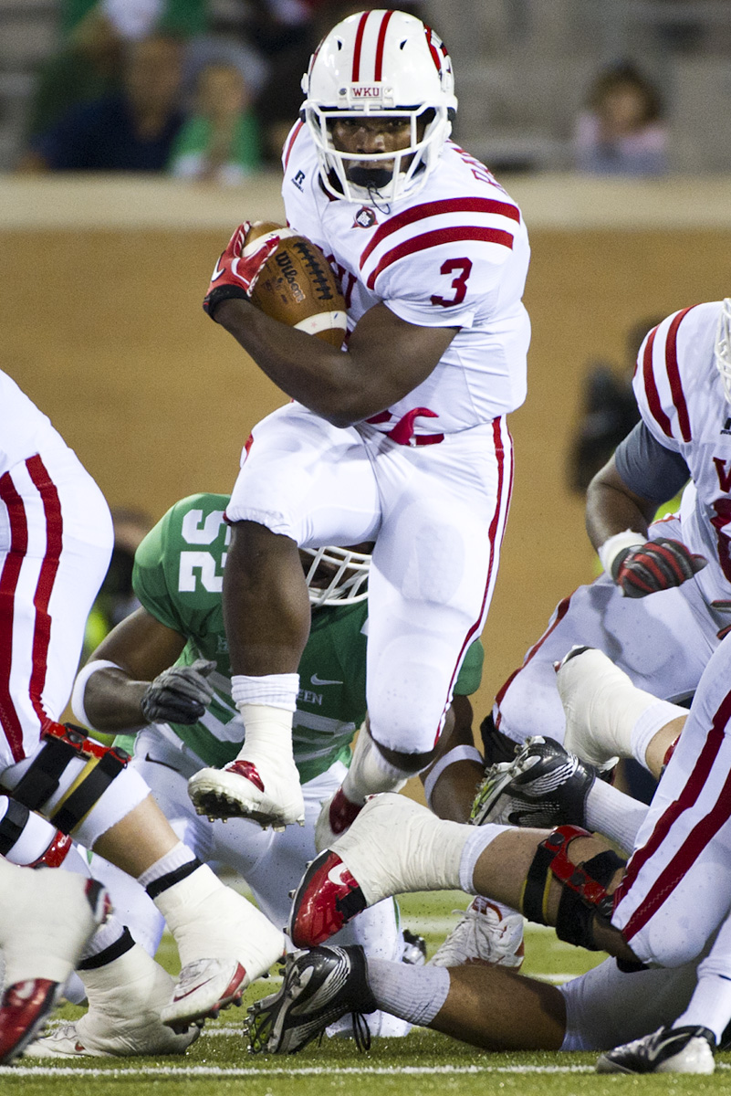 Senior running back Bobby Rainey jumps over a pileup at the line of scrimmage during a run for a short gain against North Texas at Apogee Stadium in Denton, Texas on Saturday. Rainey accumulated 262 all-purpose yards and scored two touchdowns against the Mean Green and was named the Sun Belt's Offensive Player of the Week.