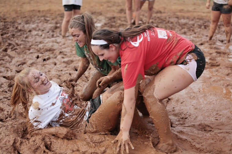 Molly Fiser, left, 19, Louisville, gets tackled to the ground by her roommate Jill Marlow, center, and her