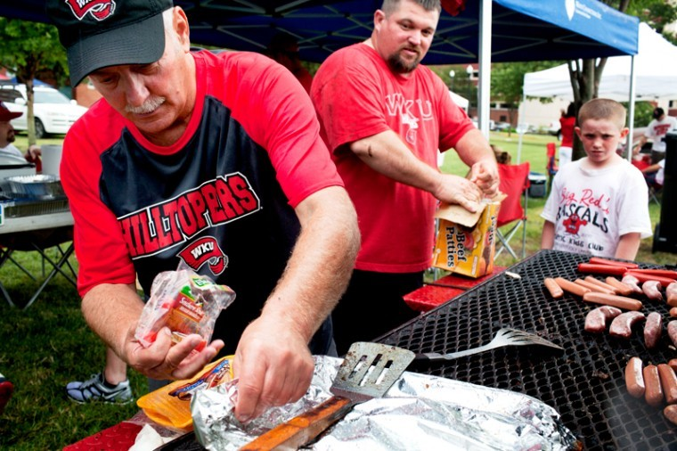 Doug Hix, left, and Dwayne Alvey, Scott's Waste employees of Bowling Green, cook hot dogs and burgers on their grill before the WKU game against Austin Peay Saturday. The Toppers went on to win 49-10 in front of a crowd of 16,237.