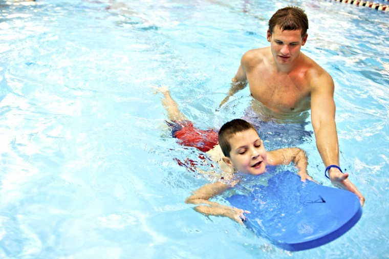 Western Kentucky swim team member Richard Russell (right), of Douglasville, Georgia, shows Logan Hansen, 7, of Bowling Green, how to use a kick board to stay afloat Saturday, Sept. 8, 2012 at the Raymond B. Preston Health & Activities Center. The swim team began its series of swim lessons to raise money for their trip to training camp in Fort Lauderdale, Florida.