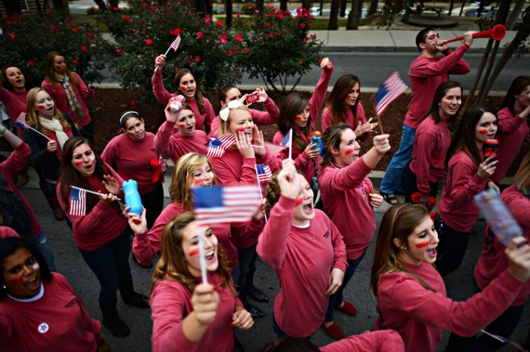 The ladies of Omega Phi Alpha stand and cheer along Ave. of Champions during the Homecoming parade Friday.