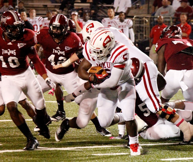 WKU running back Antonio Andrews(5) runs the ball against the Troy Trojans defense during a play at Troy University on Thursday, Oct. 11.