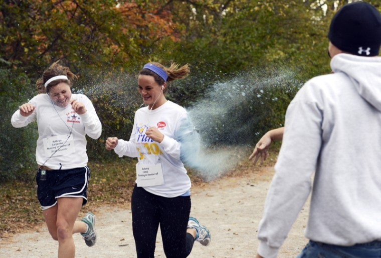 Kathryn Carpenter and Aubrey Ates run through one of the stations of color during Bowling Greens first A Color Run to Remember, put on by the WKU fraternity Phi Gamma Delta to raise money for their philanthropy, the Alzheimers Association, to assist in the fight against the prevalent disease.