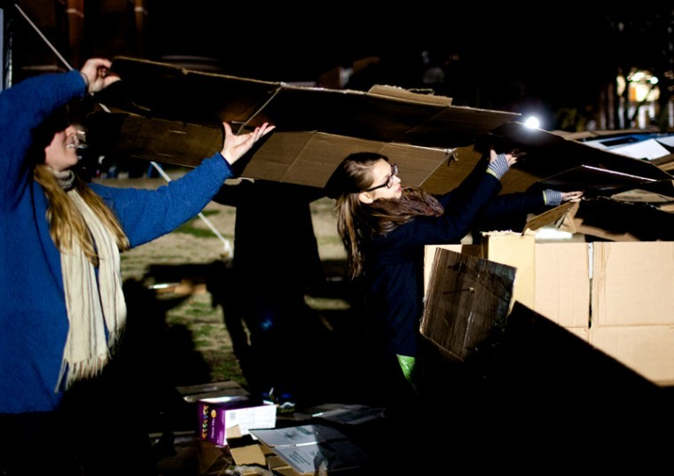 Louisville freshman Sawyer Smith, 18, carries the roof of the Minton and McCormack Hall team shelter as they complete the structure for the 22nd annual Shantytown on South Lawn Wednesday. AUSTIN ANTHONY/HERALD