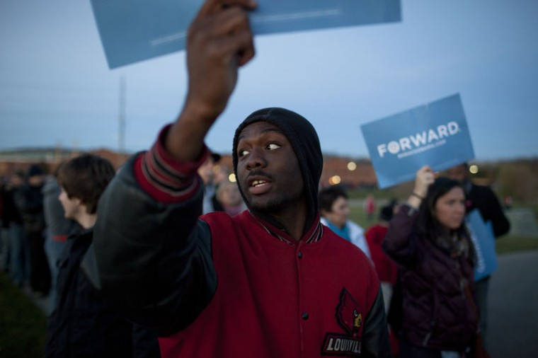 Louisville junior Miles Morton hoists an Obama sign high while in line with fellow Democratic students at the Republican rally in West Chester, Ohio. The group came to protest the rally and brought signs into the line by hiding them under their jackets.
