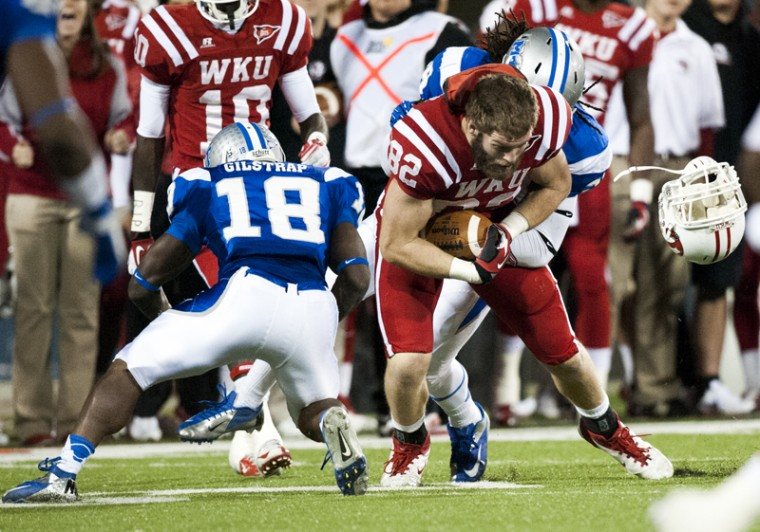 WKU tight end Jack Doyle loses his helmet after being hit byMTSU linebacker Christian Henry (behind,) and corner back Kenneth Gilstrap (18) during their game thursday at Smith Stadium. The Tops lost the game 29-34.