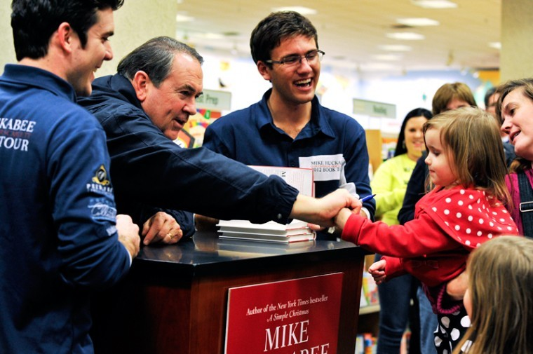 Former Presidential Candidate, former Governor of Arkansas, and TV host Mike Huckabee shakes hands with 2 year old Addie Scott while her mother Pam Scott holds her.