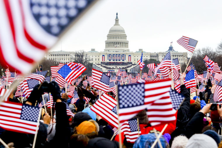 Patrons+wave+flags+at+the+National+Mall+as+President+Barack+Obama+was+introduced+at+his+ceremonial+swearing-in+at+the+U.S.+Capitol+during+the+57th+Presidential+Inauguration+in+Washington%2C+Jan.+21%2C+2013.%0A