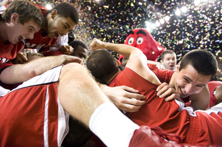 Freshman center Aleksejs Rostov hugs teammate sophomore guard Kevin Kaspar while the rest of their team celebrates their win over Florida International in the Sun Belt Conference Tournament championship.